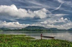 DAK LAK-越南:小组亚裔农夫去工作在Lak湖秋天时间的,少数族裔家庭,在l的草的划艇旁边 库存图片