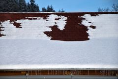 Dak met dakgoot in de winter Dak met asfaltdakspanen met sneeuw en ijskegels worden behandeld die stock foto's
