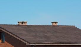 Dak met schoorstenen onder duidelijke blauwe hemel Stock Afbeelding