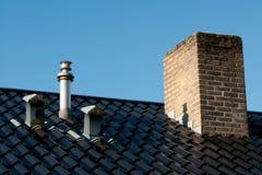 Dak met ventilatie, verwarmingspijpterminal en schoorsteen Stock Foto
