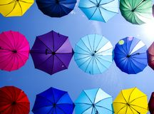 Dak van heel wat kleurrijke hangende paraplu tegen blauwe hemel stock fotografie