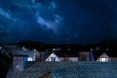 Dak van huis bij nacht met huizen op achtergrond Royalty-vrije Stock Foto