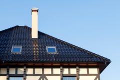 Dak van zwarte verglaasde keramische tegels met Koekoeken en ventilatiepijp Stock Foto's