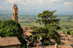 Daken en klokketoren van Palazzo-dei Priori in Montalcino, Va stock afbeelding