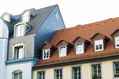 Daken van oude huizen met dakvensters en oranje daktegels in G stock foto