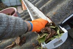 Dakgoot het Schoonmaken van Bladeren in de Herfst met hand Dakgoot het schoonmaken Goot het Schoonmaken stock afbeeldingen