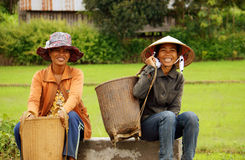 Farmer with smile sit and wait on roadsideDAKLAK,. Two woman wear hat , carry papoose ( gui) with smile on face, sit and wait on roadside at golden light Royalty Free Stock Photos
