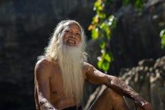 Daklak, Vietnam - 9. März 2017: Porträt des Mannes Ede-ethnischer Minderheit mit langem weißem Bart im Trachtenkleid im Wald in B stockbilder