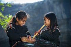 Daklak, Vietnam - 9. März 2017: Zwei kleine Mädchen Ede-ethnischer Minderheit, die lernen, die Flöte im Wald zu spielen das Ede,  lizenzfreie stockfotos