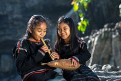 Daklak, Vietnam - Mar 9, 2017: Two Ede ethnic minority little girls learning to play the flute in forest. The Ede have long lived. In the Tay Nguyen or high royalty free stock photography