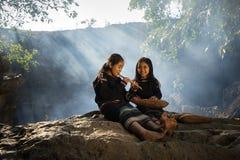 Daklak Vietnam - Mars 9, 2017: Två små flickor Ede för etnisk minoritet som lär att spela flöjten i skog som Eden har länge bott arkivfoto
