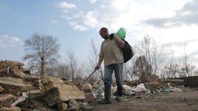 Dakloos mannetje die naar plastiek bij afvalplaats zoeken stock footage