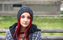 Dakloos meisje, Jong rood haarmeisje alleen in openlucht met hoed zitten en bezorgd en gedeprimeerd overhemd die nadat zij dakloz stock afbeelding