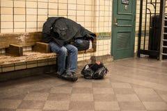 Dakloze die mensenslaap op de bank in de post van de de Stadsmetro van New York door eigen laag wordt behandeld Royalty-vrije Stock Foto's