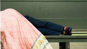 Dakloze mens die bij de bank liggen stock foto's