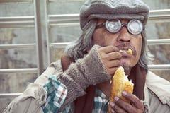 Dakloze mens die oud brood op gangstraat eten royalty-vrije stock afbeeldingen