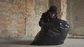 Dakloze mens gevonden telefoon in de vuilniszak stock video