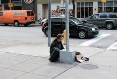 Dakloze mens gezien zitting door de kant van een weg die in een bezige stad kruisen Stock Foto's