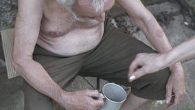Dakloze mens met een kop die om schenking vragen stock video