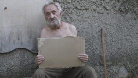 Dakloze mens met een teken die om hulp vragen stock video