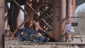 Dakloze mensenslaap onder de brug stock footage