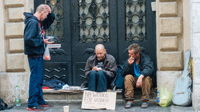 Dakloze mensenzitting en holding een fles Royalty-vrije Stock Foto's