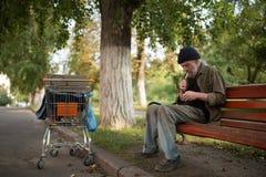 Dakloze mensenzitting op de sigaret van de bankbliksem Stock Fotografie