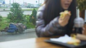 Dakloze persoon die op straat terwijl gelukkige jonge vrouw die hamburger eten in koffie liggen stock videobeelden