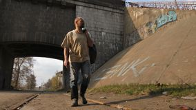 Dakloze rijpe mens die dichtbij brug lopen stock video