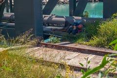Dakloze slaap op de brug stock foto
