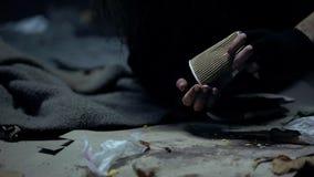 Dakloze vrouw die muntstukken van document kop werpen, die schenkingen, liefdadigheid tellen stock foto