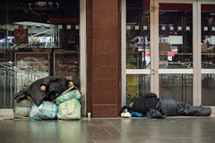 Dakloze vrouwenslaap op de zakken en de enveloppen stock fotografie