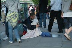 Dakloze zitting op een bestrating Stock Afbeeldingen