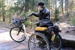 Daklozen in een rolstoel die op een bosweg gaan De three-wheeled rolstoel is uitgerust met een doos voor dingen Ongewassen royalty-vrije stock afbeeldingen