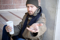 Daklozen gezet in de straat en het vragen om liefdadigheid Stock Afbeeldingen