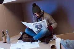 Daklozen met bedrijfskrant stock foto's