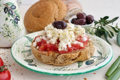 Dakos traditional greek appetizer on a traditional plate with ceramic olive oil jar, dry rye bread, olives and olive branch. Royalty Free Stock Photography