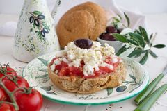 Dakos traditional Greek appetizer on a traditional plate with ceramic olive oil jar, dry rye bread, olives and olive branch. Stock Image