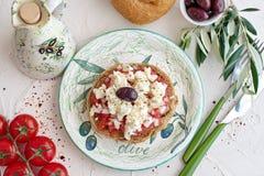 Dakos traditionelles Greekappetizer auf einer traditionellen Platte mit keramischem Olivenölglas, trockenem Roggenbrot, Oliven un stockfotos