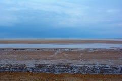 Dakspaan rotsachtig strand van de kust van Norfolk en donkerblauwe hemel, Noordelijke Overzees, Holkham-strand, het Verenigd Koni Stock Afbeelding