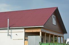 Dakwerkbouw met de rode tegels van het metaaldak en metaalschoorsteen in openlucht Stock Foto