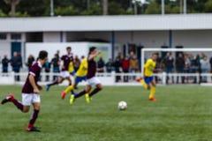 Dal colpo del fuoco degli adolescenti che giocano a calcio calcio sul fotografia stock