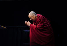 Dalai Lama. The Dalai Lama kneels and offers a gesture of respect to the crowd he is speaking to during a talk he gave at Middlebury College on October 13, 2012 Royalty Free Stock Photos
