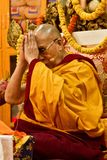 Dalai Lama lyfter hans händer i bön, som han undervisar i Dharamsala, Indien, Septemeber Julian_Bound 2014 Arkivbilder