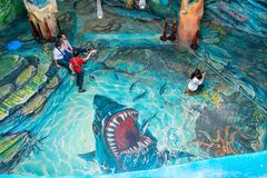 DALAT, VIETNAM - APRIL 15, 2019: Tourists sit on a painted floor with mouth of shark in Crazy House in Dalat Vietnam stock images