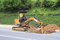 Worker  tracked excavator on the street asphalt  for road repairing Royalty Free Stock Photo