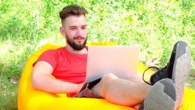 Daleka praca na internecie w świeżym powietrzu Nowożytny faceta biznesmena freelancer z laptopu lying on the beach na pomarańczow zdjęcie wideo