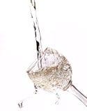 Dalend water in het glas op wit stock foto's