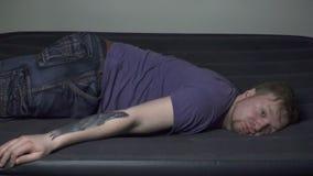 Dalende blonde mens op opblaasbare matras stock footage
