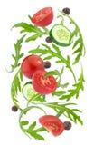 Dalende groentensalade Kersentomaten, rucola en komkommer op witte achtergrond worden geïsoleerd die royalty-vrije stock afbeelding